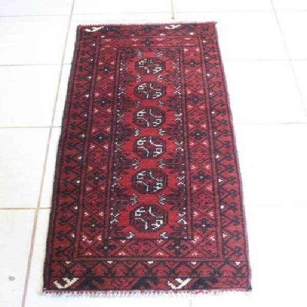 A stylish persian hand made runner carpet (140cm x 52cm).
