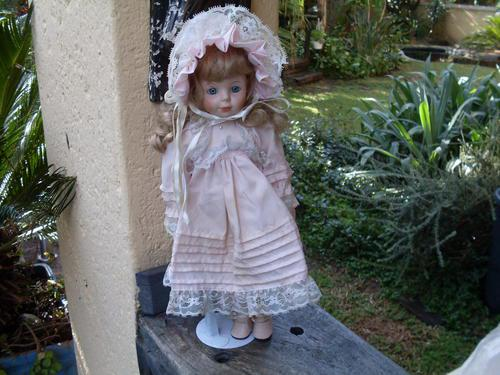 Collectors porcelain blonde blue eyed girl doll on a stand
