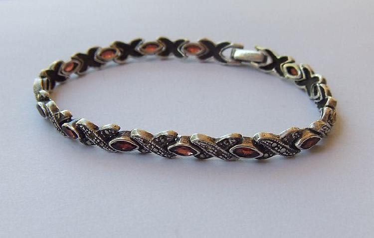 An eye catching sterling silver bracelet set with faceted